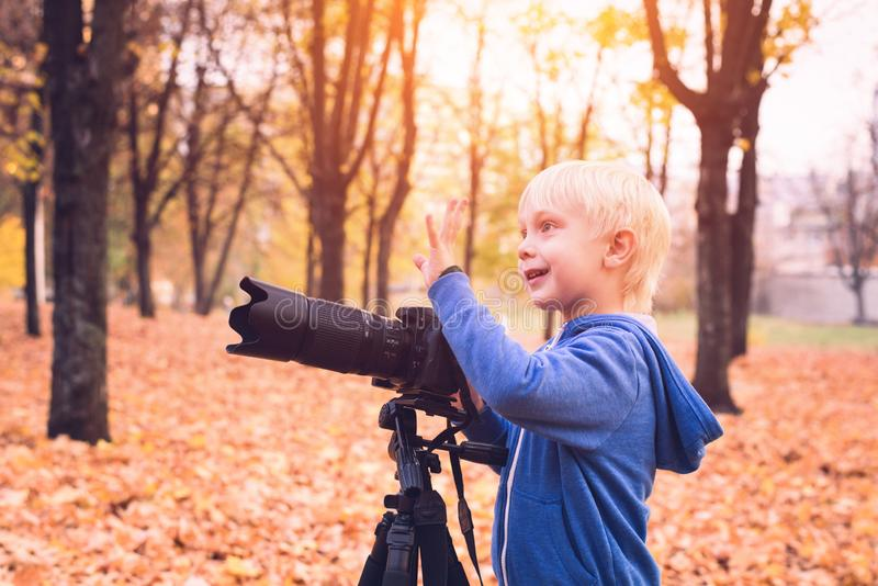 Little blond boy shoots with a large SLR camera on a tripod. Photo session in the autumn park royalty free stock photos