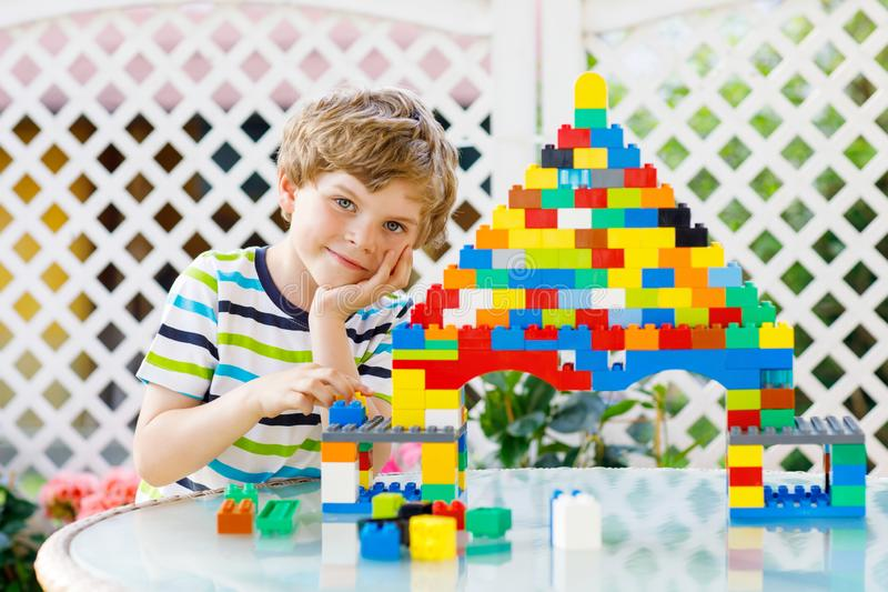 Little blond child and kid boy playing with lots of colorful plastic blocks. royalty free stock photo