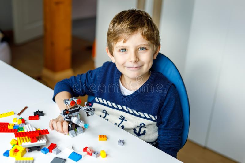 Little blond kid boy playing with lots of colorful plastic blocks. royalty free stock photo