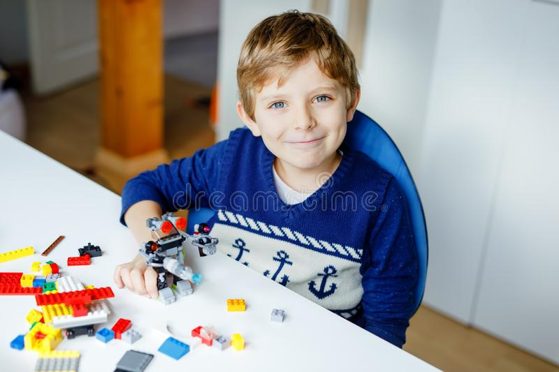 Little blond child playing with lots of colorful plastic blocks. Cute school kid boy having fun with building and stock image