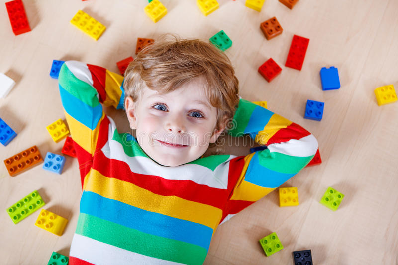 Little blond child playing with lots of colorful plastic blocks. Indoor. Kid boy wearing colorful shirt and having fun with building and creating royalty free stock images