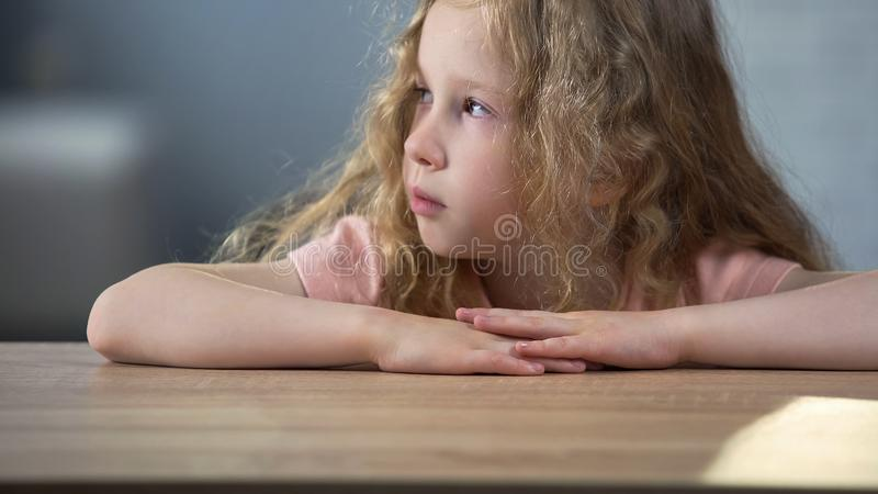 Little blond curly sad girl sitting at table and thinking about own behavior stock photos