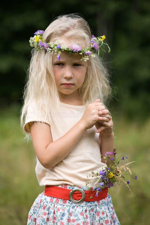Little blond flicka i blommakran royaltyfria foton