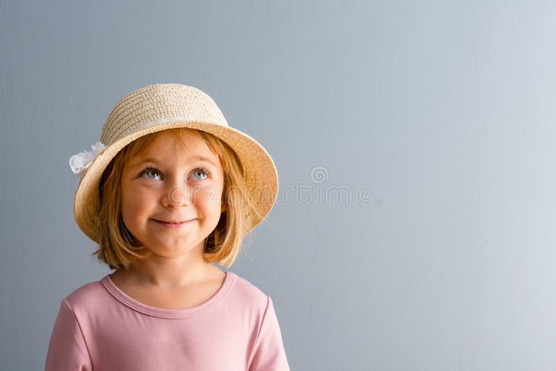 Little blond girl daydreaming with happy smile stock photo