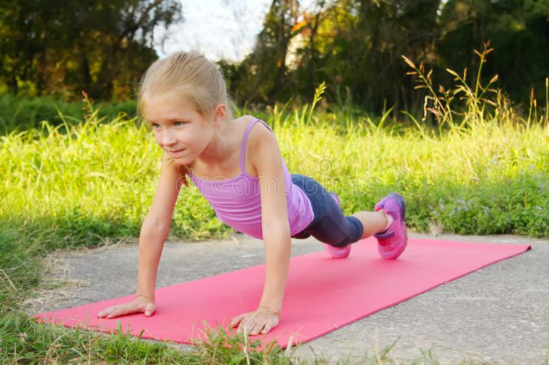 Little blond girl doing fitness exercises plank in the park royalty free stock photo