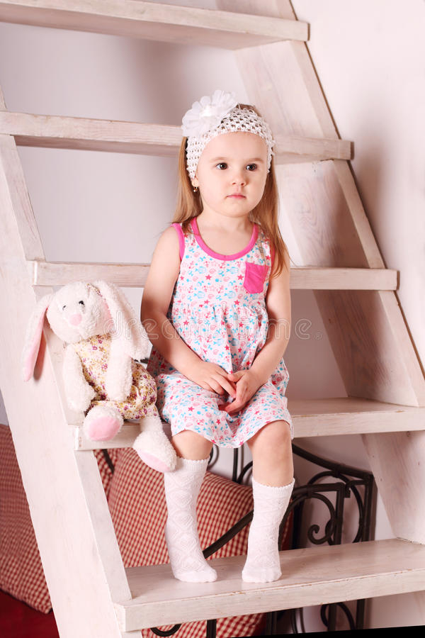 Little blond girl in dress sitting on wooden stairs with so stock images