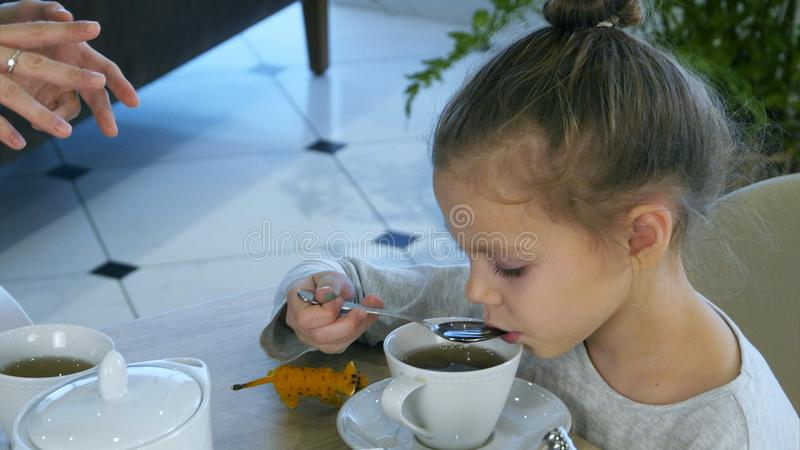 Little blond girl drinking tea from spoon while her parents are busy with tablet. stock images