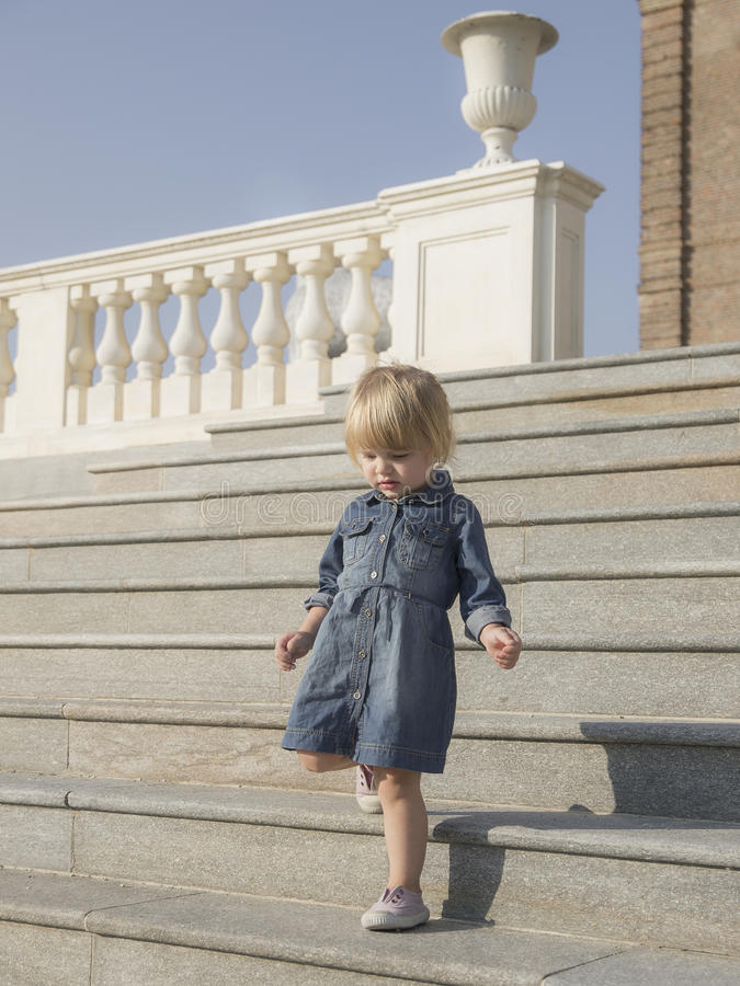 Little blond girl goes down the staircase stock images