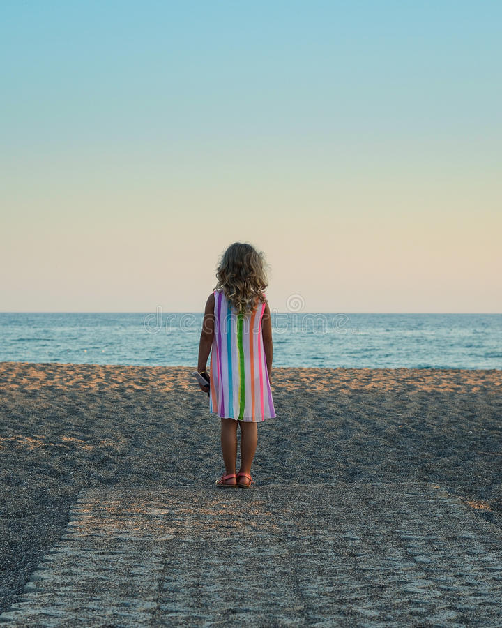 Little blond girl looking at the sea royalty free stock photos