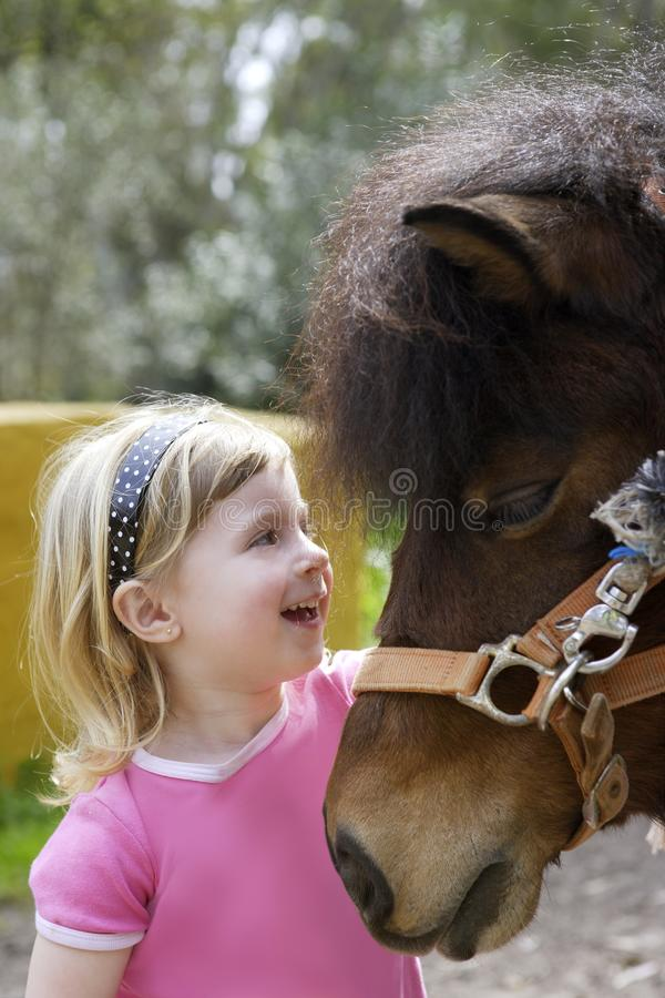 Little blond girl loves her donkey funny portrait. Little blond girl loves her pony funny portrait royalty free stock image