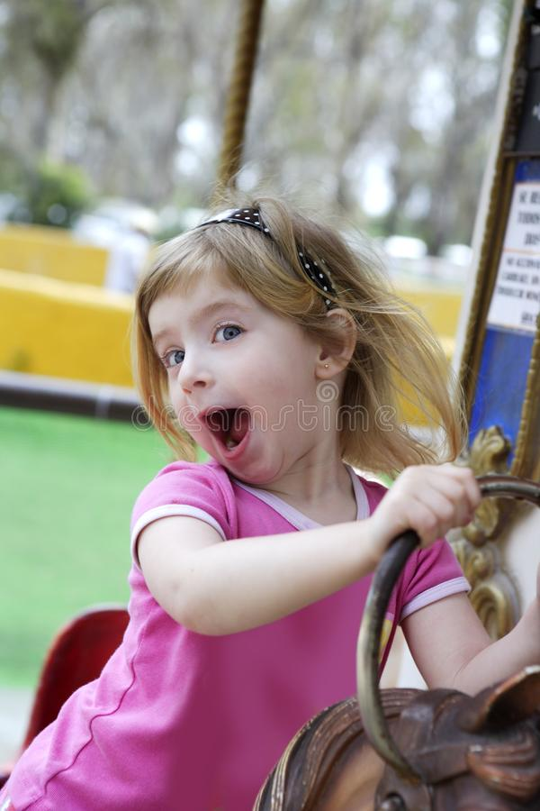 Little blond girl playing horses merry go round. Funny happy gesturing little blond girl playing on horses merry go round stock image
