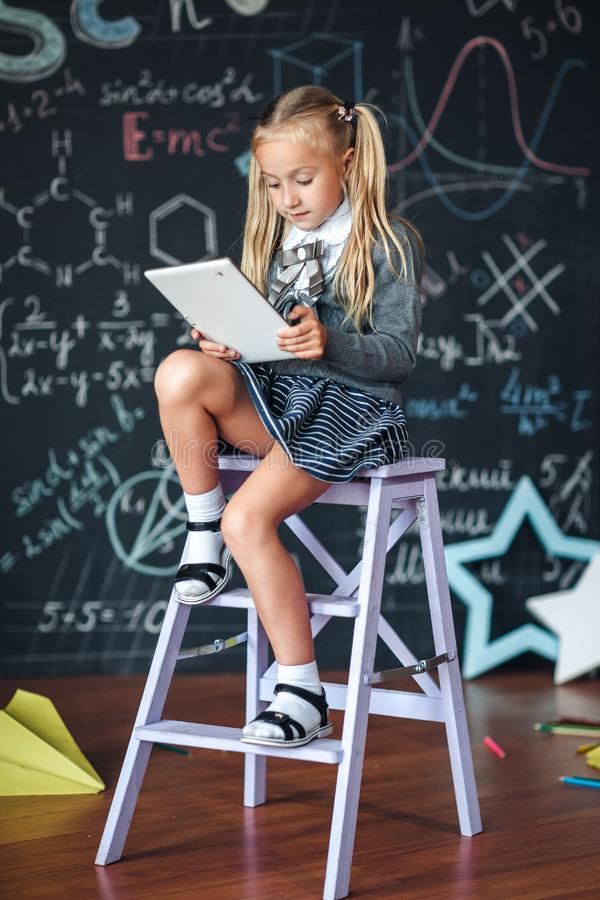 Little blond Girl in school uniform holding white tablet pc in chemistry class. Chalkboard with school formulas background royalty free stock photo