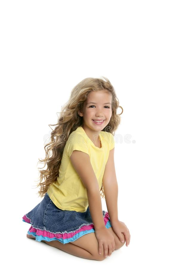 Little blond girl smiling portrait on her knees royalty free stock photo