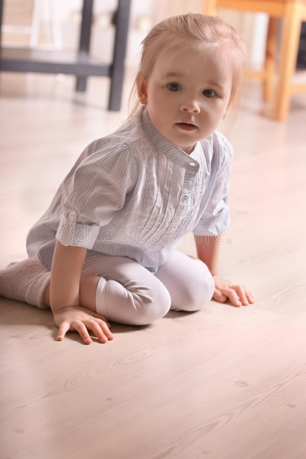 Little blond girl in striped shirt sitting on wooden floor royalty free stock photo