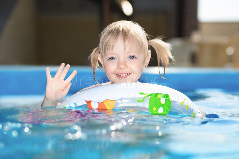 Little blond girl swimming in water pool stock photography