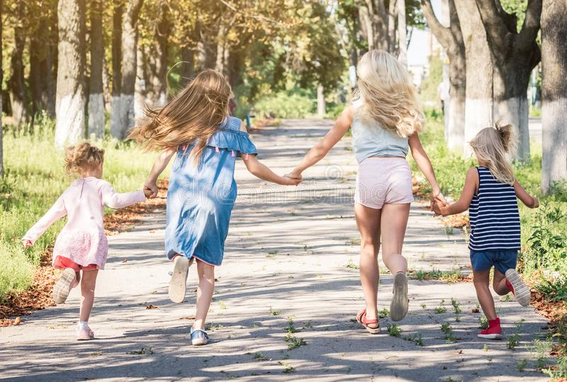 Little smiling girls running on the sunshine autumn alley by holding hands royalty free stock photos