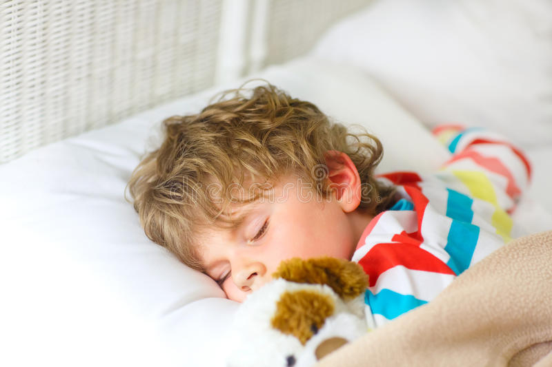 Little blond kid boy in colorful nightwear clothes sleeping royalty free stock images