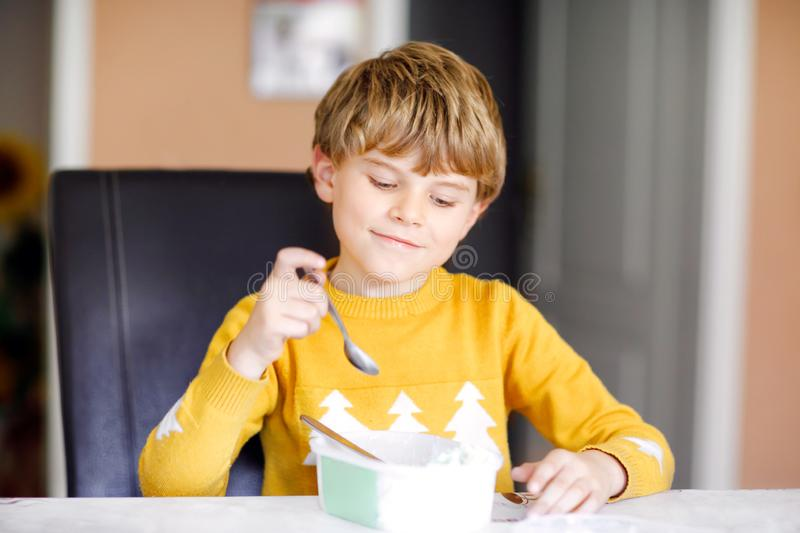 Little blond kid boy with curly hairs eating ice cream at home or in kindergarten. Beautiful child with big icecream box royalty free stock image
