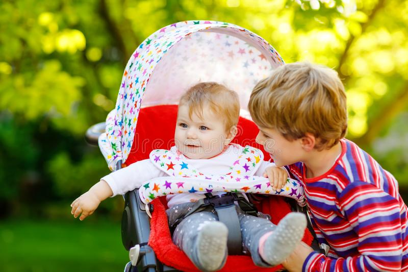 Little blond kid boy playing with baby sister. Happy siblings in garden. Baby girl sitting in pram or stroller. Brother. And cute toddler outdoors, on summer royalty free stock photos