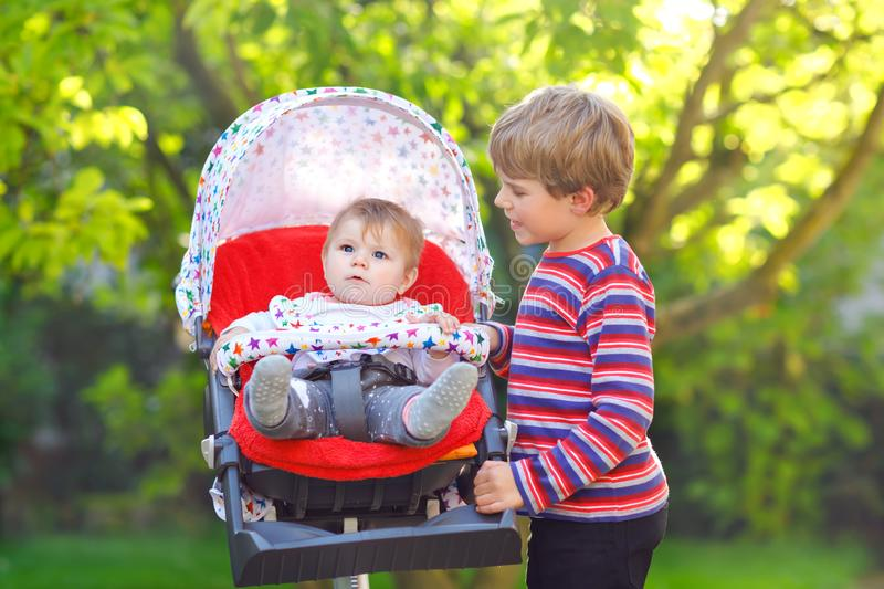 Little blond kid boy playing with baby sister. Happy siblings in garden. Baby girl sitting in pram or stroller. Brother. And cute toddler outdoors, on summer royalty free stock photo