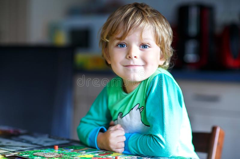 Little blond kid boy playing together board game at home. Funny child having fun stock photos
