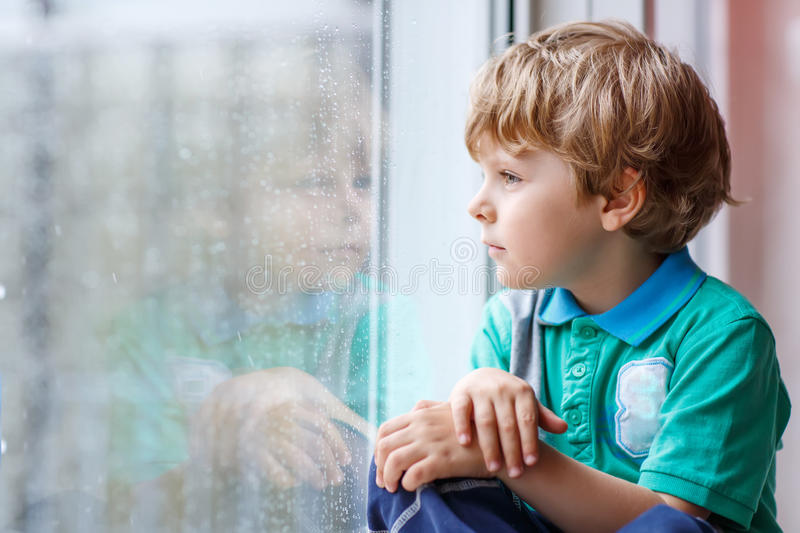 Little blond kid boy sitting near window and looking on raindrop stock images