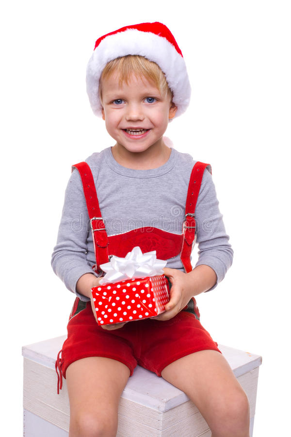 Little blond kid in red costume of dwarf holding gift box with ribbon. Christmas royalty free stock photo