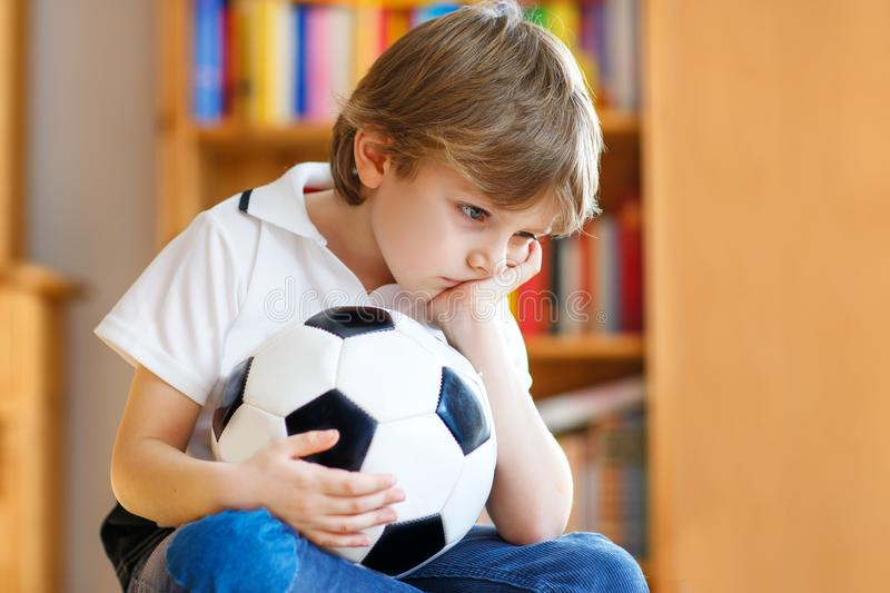 Sad and not happy little kid with football about lost football or soccer game. child after watching match on tv. Little blond preschool kid boy with ball royalty free stock photo