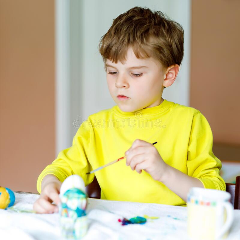 Little blond preschool kid boy coloring eggs for Easter holiday in domestic kitchen, indoors. Child having fun with stock photo