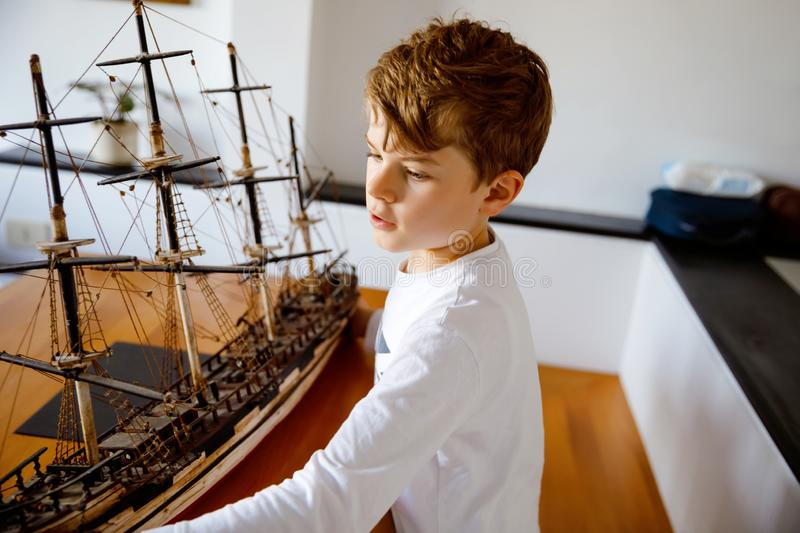 Little blond school kid boy playing with sailing ship model indoors. Excited child with yacht having fun after school at. Home. Happy boy building and creating royalty free stock photos