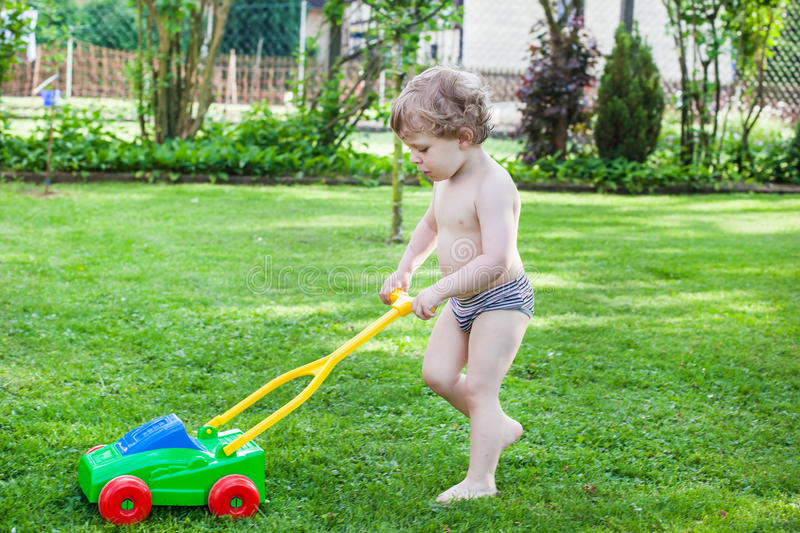 Little blond toddler boy playing with lawn mower stock images