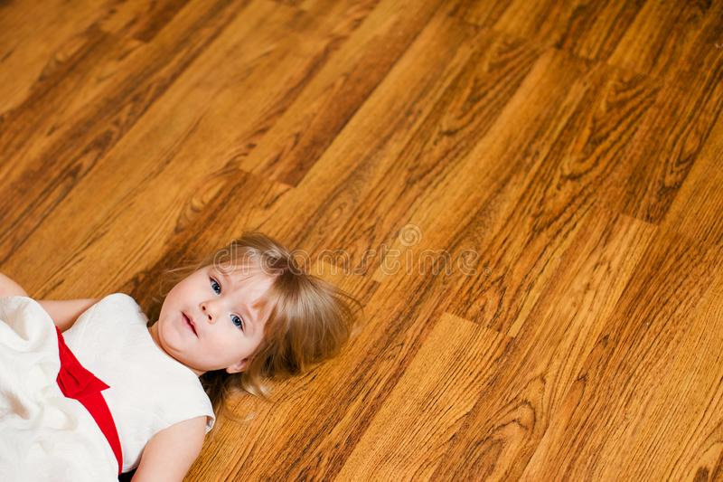Little blonde baby girl two years old with big pink and white balloons lying on the wooden floor on her birthday party royalty free stock photo