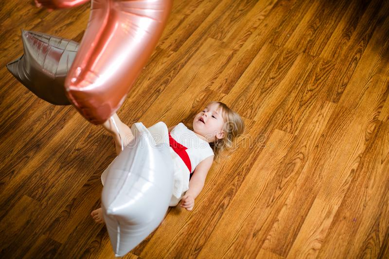 Little blonde baby girl two years old with big pink and white balloons lying on the wooden floor on her birthday party royalty free stock photos