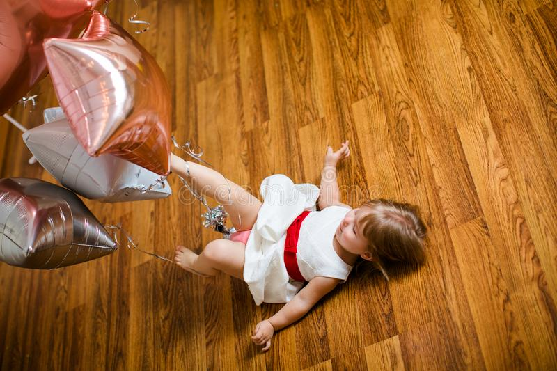 Little blonde baby girl two years old with big pink and white balloons lying on the wooden floor on her birthday party royalty free stock image