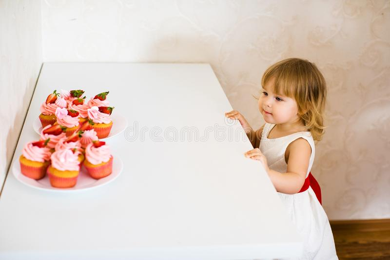 Little blonde baby girl two years old in white dress looking at her birthday cake and different pin sweets on the table stock photos