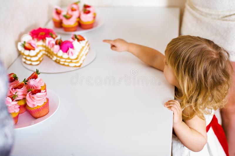 Little blonde baby girl two years old in white dress looking at her birthday cake and different pin sweets on the table stock photo