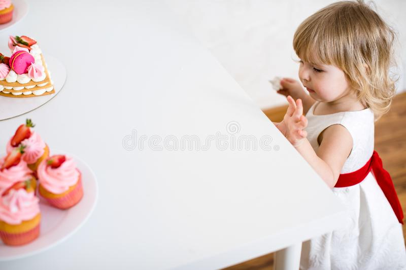Little blonde baby girl two years old in white dress looking at her birthday cake and different pin sweets on the table royalty free stock image