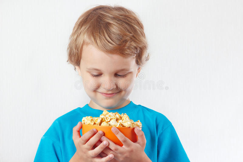 Little blonde boy looking for a bowl of popcorn royalty free stock images