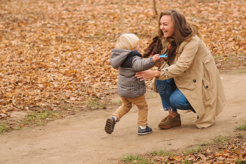 Little blonde boy running to his mother in embracing. Happy mother and child on autumn walk. Autumn weather. Family, fashion, royalty free stock photos