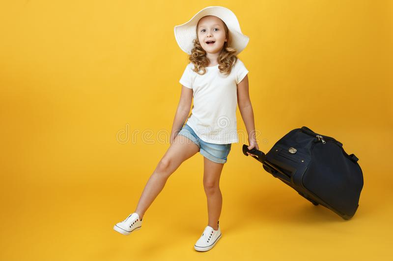 A little blonde child girl dreams of traveling and goes with a suitcase. Yellow background stock images