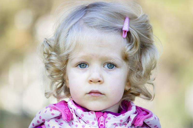 Little blonde curly hair girl stock photography