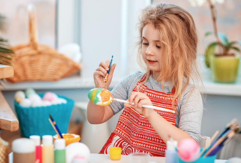 Little blonde girl coloring eggs for Easter holiday at home stock photos