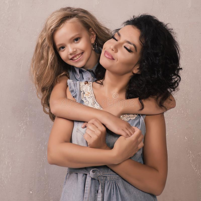 A little blonde girl in a denim dress hugs her mom brunette from behind. royalty free stock image