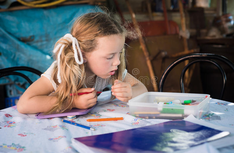 Little blonde girl drawing with crayons royalty free stock images