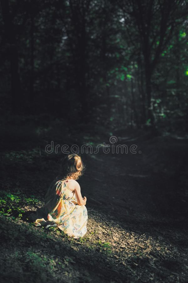 Little blonde girl in dress sits in sun light inside a dark creepy forest looking away to the trail. Girl alone in the woods stock image