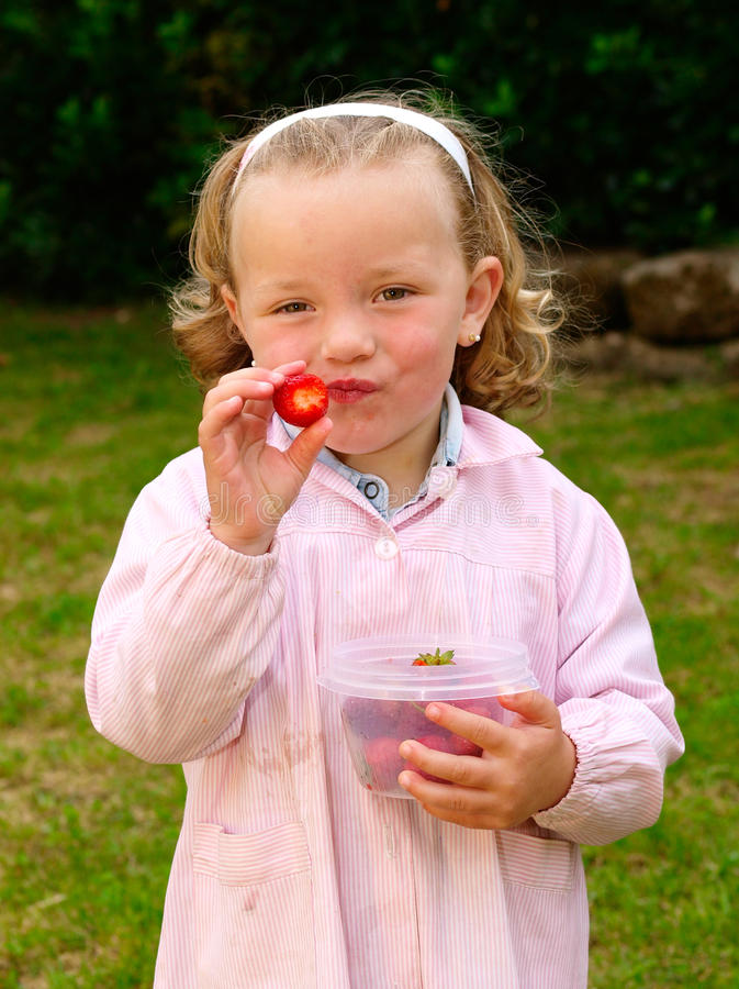Little blonde girl eating strawberries royalty free stock photography