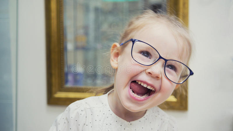 Little blonde girl in hall of ophthalmology clinic have fun and plays with glasses. Close up royalty free stock images