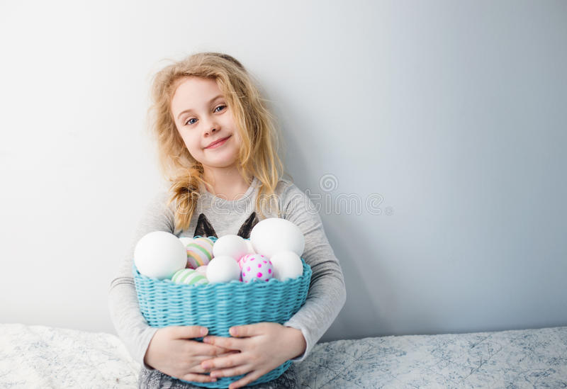 Little blonde girl holding basket with painted eggs. Easter day. royalty free stock images