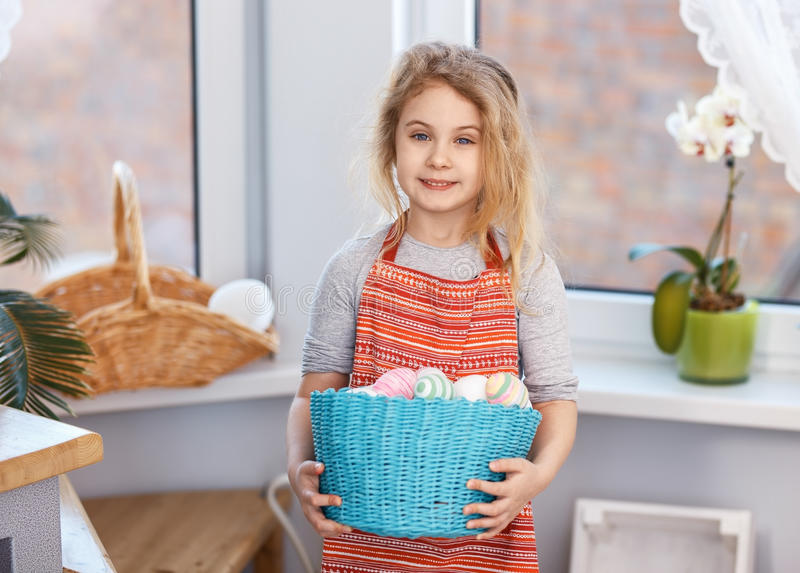 Little blonde girl holding basket with painted eggs. Easter day. stock photos