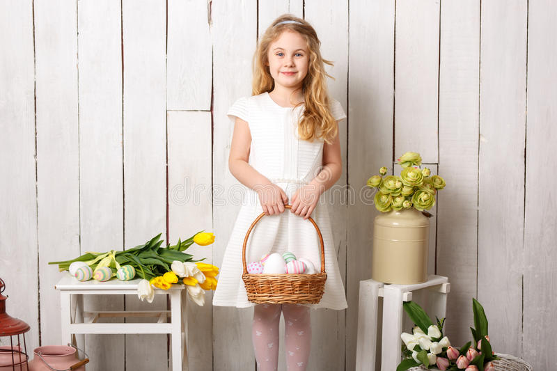 Little blonde girl holding basket with painted eggs. Easter day. royalty free stock photography